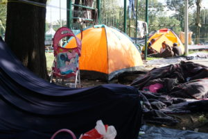 Some individuals in the caravan had tents. Others made do with tarps and blankets hung up with rope and telephone wires. The Ciudad Deportiva is scattered with strollers, teddy bears, and other belongings of children and families. Photo by Lily Folkerts.